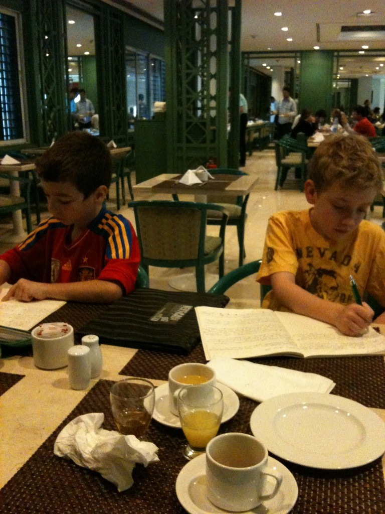 Callum and Declan doing schoolwork in the hotel lobby